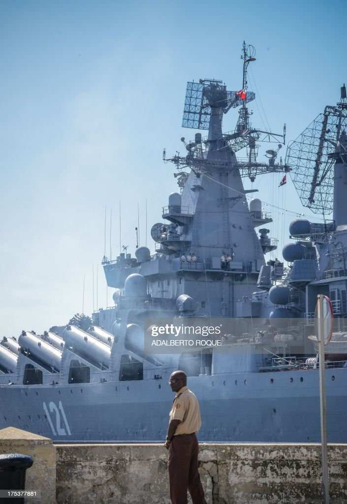 Cuban policemen stand watch as the 'Moskva' Russian guide missile cruiser moors at Havana's harbour, on August 3, 2013. The vessel is part of a three-ship group in official visit to Cuba. AFP PHOTO/Adalberto ROQUE