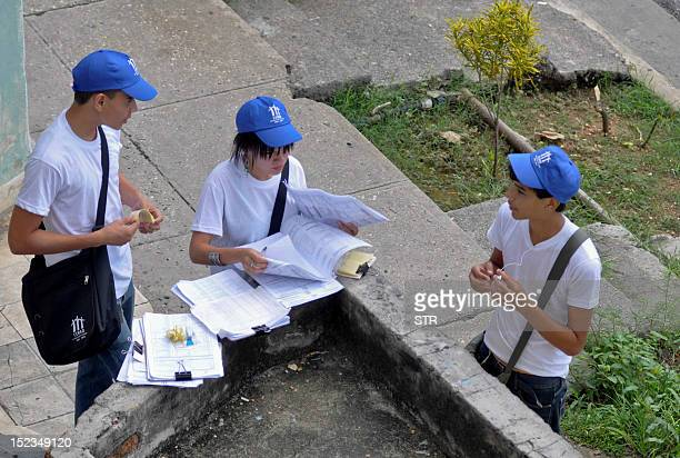 Cuban pollsters read an application forms as they arrive to a house in Havana as part of the national census on September 19 2012 Fiftyfive thounsand...