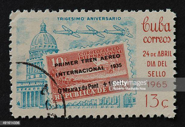 Cuban postage stamp celebrating the stamp day and the first aerial train A large red square with black letters partially covers a blue ink drawing of...