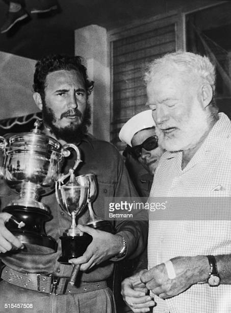 Cuban Premier Fidel Castro holds the three cups he won in the Hemingway fishing tournament that ended here May 15th At right is novelist Ernest...