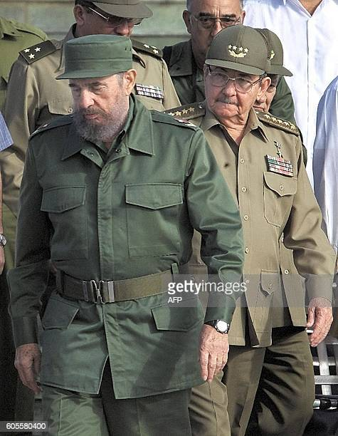 Cuban President Fidel Castro is watched by his brother Minister of the the Revolutionary Armed Forces Raul Castro 02 December 2001 during the 45th...