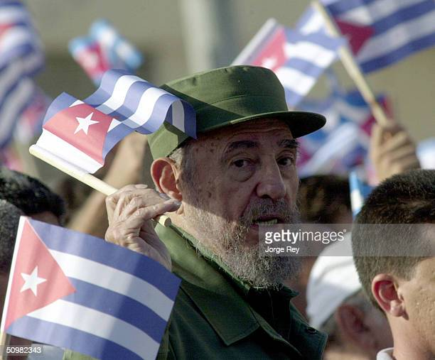 Cuban President Fidel Castro waves a Cuban flag during a demonstration outside the US Interest Section June 21 2004 in Havana Cuba Castro addressed...
