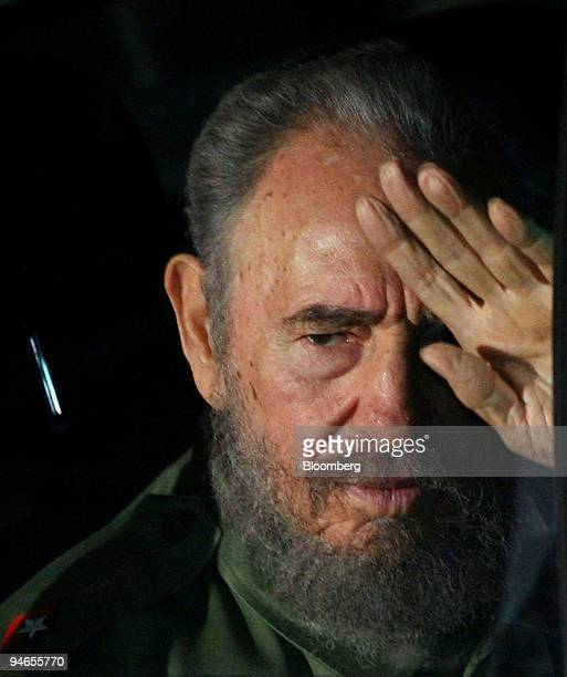 Cuban President Fidel Castro waves from his car upon his arrival at the airport for the Mercosur Trade Summit in Cordoba Argentina on Thursday July...