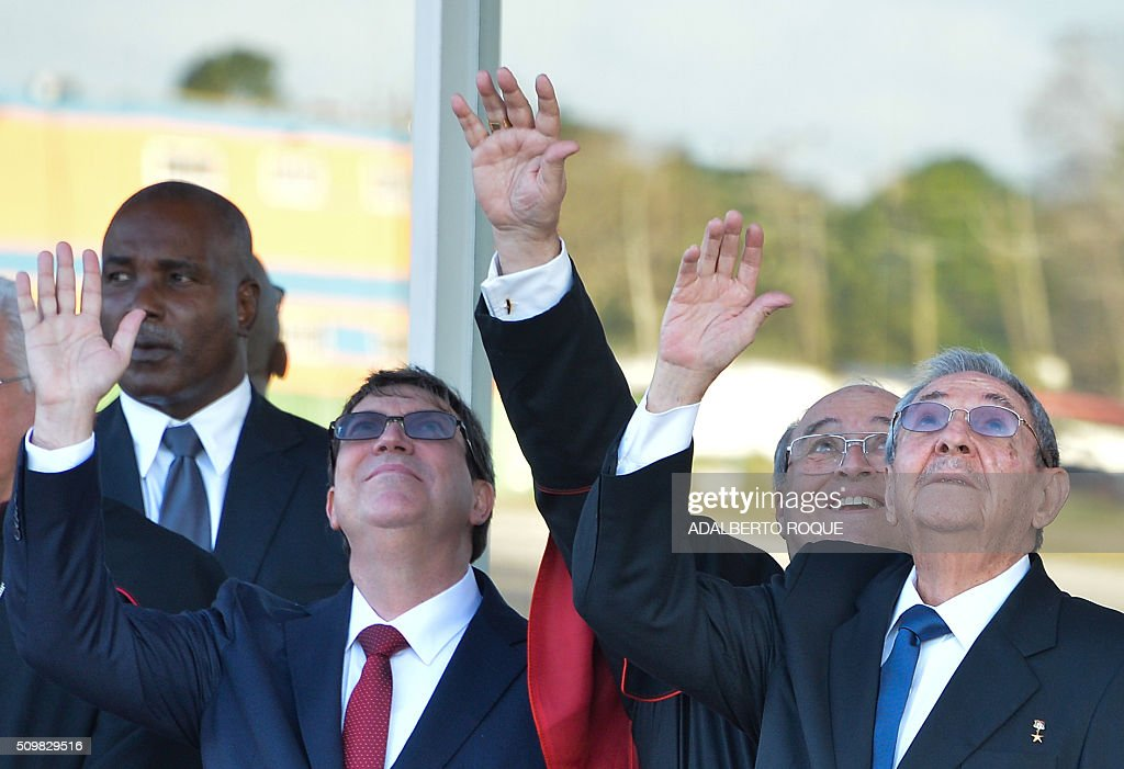 Cuban President Raul Castro (R) and Cuban Cardinal Jaime Ortega (2nd R) wave to Pope Francis at Jose Marti International Airport in Havana as his plane takes off for Mexico on February 12, 2016. Pope Francis and Russian Orthodox Patriarch Kirill kissed each other and sat down together Friday at Havana airport for the first meeting between their two branches of the church in nearly a thousand years. AFP PHOTO/ADALBERTO ROQUE / AFP / ADALBERTO ROQUE