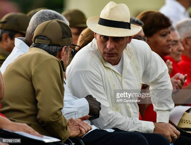 Cuban president Raul Castro and Cuban First Vice President Miguel DiazCanel talk during the celebration of the 64th anniversary of the guerrilla...