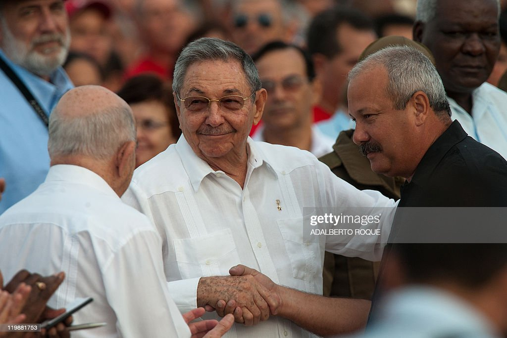 Cuban President Raul Castro (C) and First Vice-President Jose Ramon Machado Ventura (L) greet the first secretary of the Communist Party Jorge Luis Tapia, during the celebrations for the 58th anniversary of the Moncada barrack attack, at Revolution Square in Ciego de Avila, in the Cuban province of the same name, on July 26, 2011.