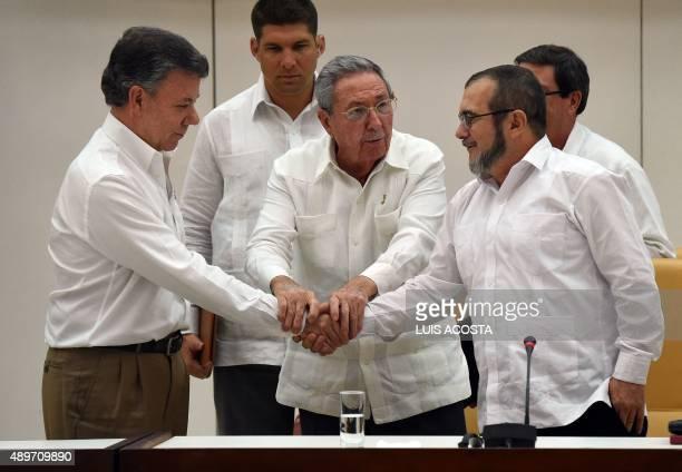 Cuban President Raul Castro Colombian President Juan Manuel Santos and the head of the FARC guerrilla Timoleon Jimenez aka Timochenko shake hands...