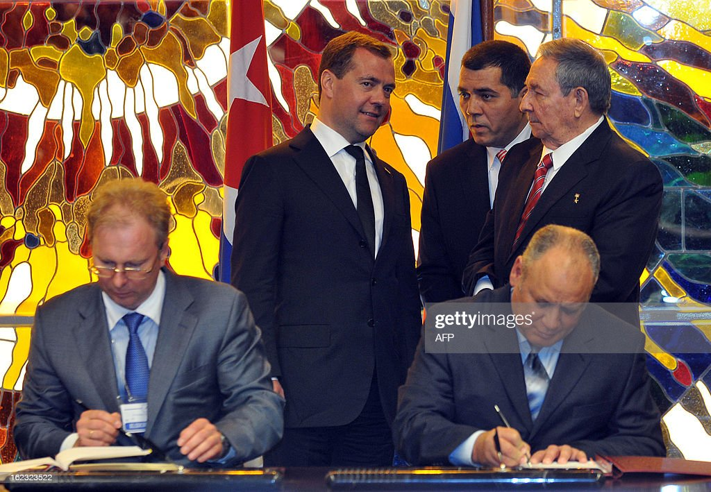 Cuban President Raul Castro (R-background) confers with Russian Prime Minister Dmitry Medvedev (L-background) during the signing of bilateral agreements on February 21, 2013 in Havana. Signing the agreements are Russian Foreign Minister Seguei Ryabkov (L) and Cuban Vice president Ricardo Cabrisas (R). Medvedev is in Cuba on an official 2 day visit. AFP PHOTO / POOL / Ernesto Matrascusa