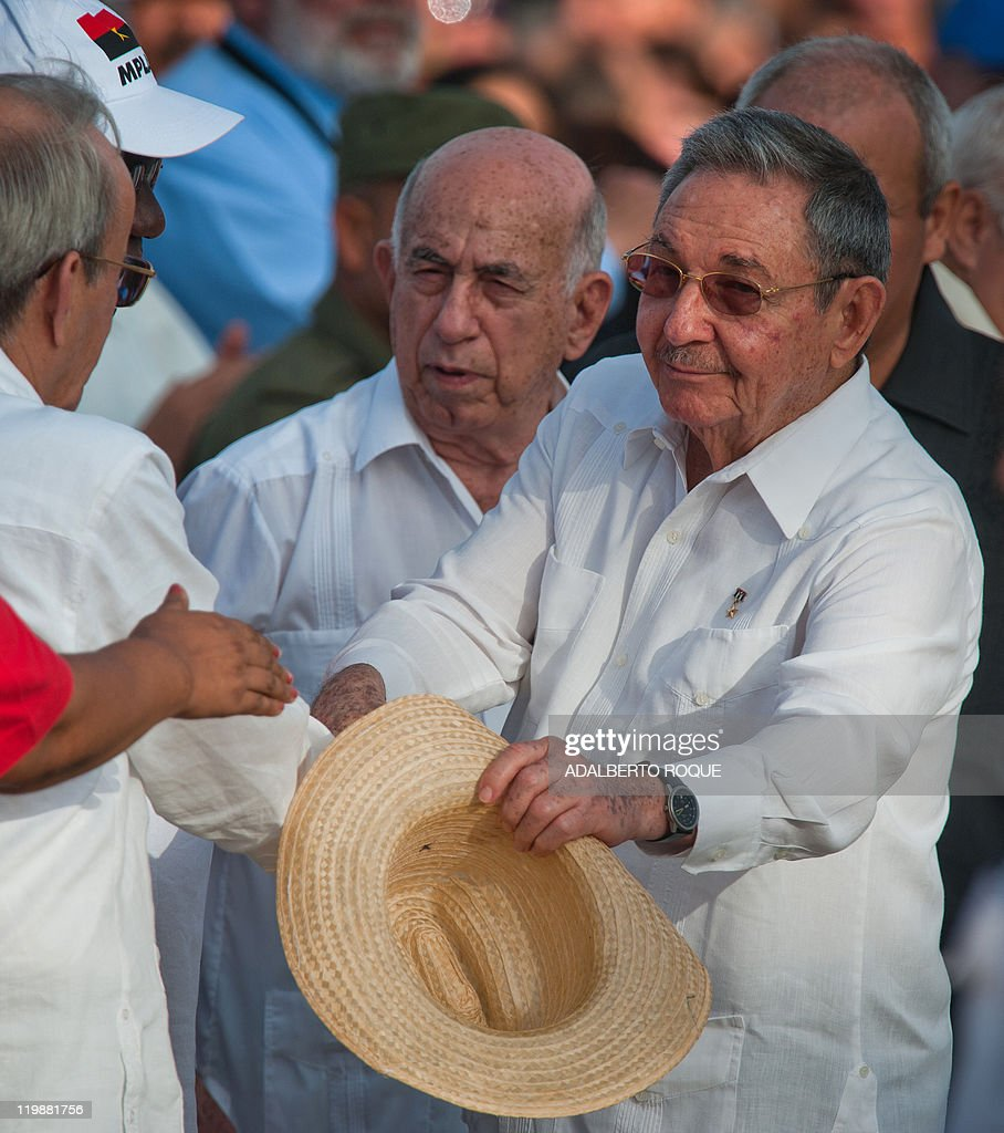 Cuban President Raul Castro (R) greets Parliament President Ricardo Alarcon (L), as First Vice-President Jose Ramon Machado Ventura (C) looks on, during the celebrations for the 58th anniversary of the Moncada barrack attack, at Revolution Square in Ciego de Avila, in the Cuban province of the same name, on July 26, 2011. AFP PHOTO/ADALBERTO ROQUE