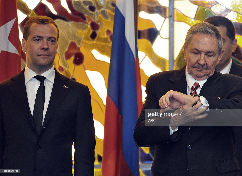 Cuban President Raul Castro (R) looks at his watch beside Russian Prime Minister Dmitry Medvedev (L) during the signing of bilateral agreements on February 21, 2013 in Havana. Medvedev is in Cuba on an official 2- day visit. AFP PHOTO / POOL / Ernesto Matrascusa