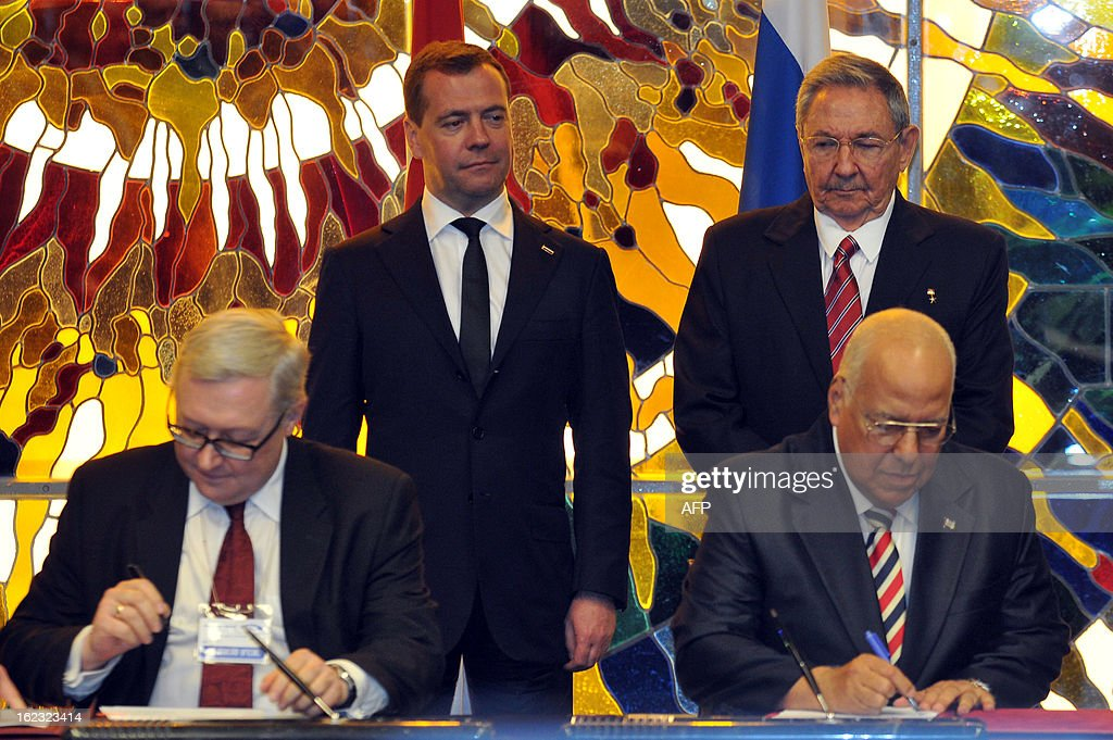 Cuban President Raul Castro (R-background) stands with Russian Prime Minister Dmitry Medvedev (L-background) during the signing of bilateral agreements on February 21, 2013 in Havana. Signing the agreements are Russian Foreign Minister Seguei Ryabkov (L) and Cuban Vice president Ricardo Cabrisas (R). Medvedev is in Cuba on an official 2-day visit. AFP PHOTO / POOL / Ernesto Matrascusa