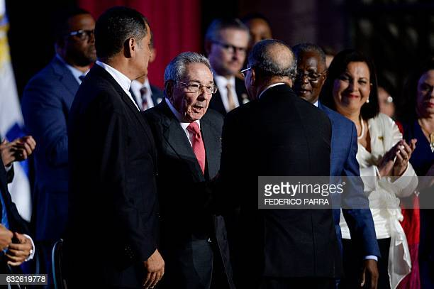 Cuban President Raul Castro talks with Dominican President Danilo Medina and Ecuadorean President Rafael Correa during the opening ceremony of the...