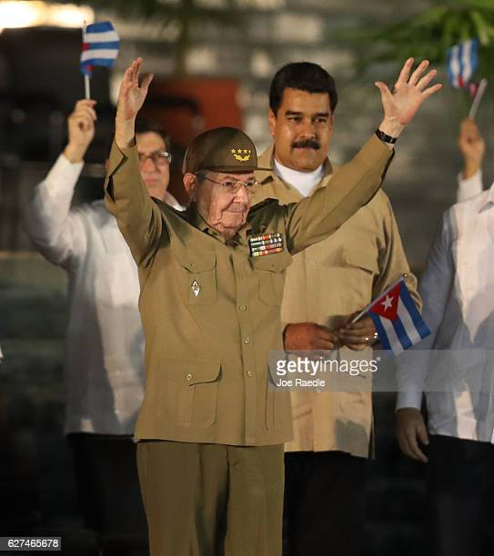 Cuban President Raul Castro waves to the crowd as Venezuela's President Nicolas Maduro stands behind him during a memorial tribute for former...
