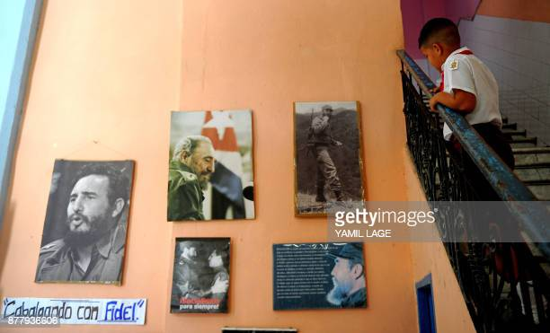 A Cuban primary school student looks at a wall decorated with posters of late Cuban leader Fidel Castro in Havana on November 23 2017 Cuba...