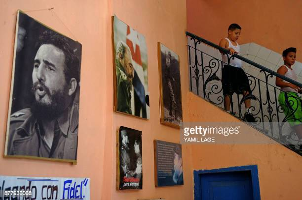 Cuban primary school students walk down the stairs next to wall decorated with posters of Cuban late leader Fidel Castro in Havana on November 23...
