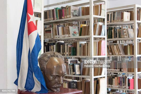 Cuban public library Jose Marti bust and Cuban flag decorating shelves full of books