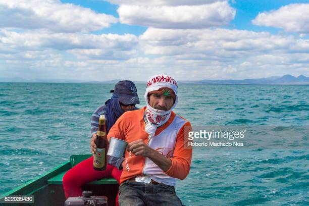 Cuban real fishermen in a recreational outing Sailor in scarf sitting with another man in small green boat in middle of sea holding a rum bottle and...