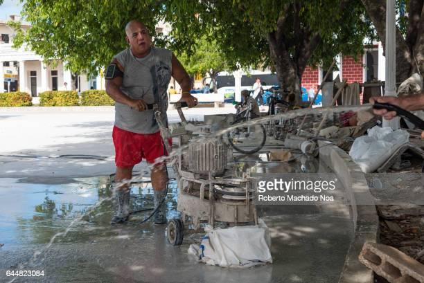 Cuban real people lifestyle man polishing Calixto Garcia plaza granite floor with rustic homemade equipment