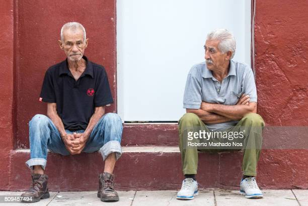Cuban real people lifestyles friends sitting in sidewalk doing nothing Two old men in tshirt and pants sitting quietly in front red and white wall
