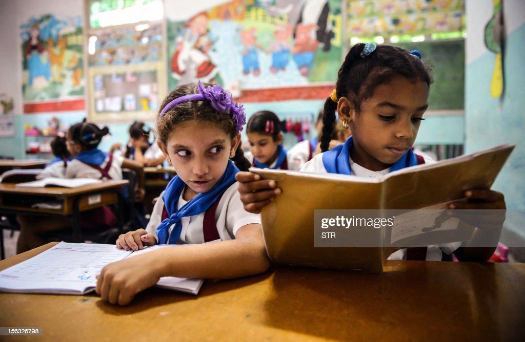 Cuban schoolgirls read during class, on November 13, 2012, in Havana.