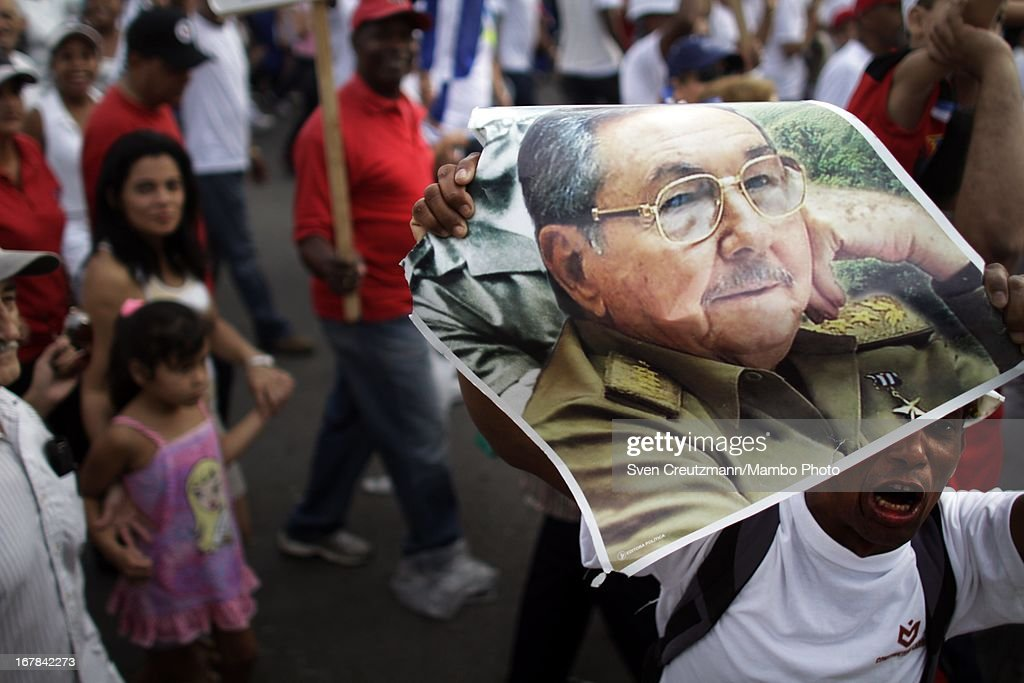 A Cuban screams as he holds a photo of Cuba's president Raul Castro, brother of Revolution leader Fidel Castro, during the annual May Day parade of hundreds of Cubans at the Revolution Square on May 1, 2013 in Havana, Cuba. Former president Fidel Castro last attended a May Day parade in 2006, before he fell ill, just two months later.