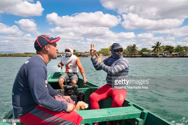 Cuban self employed fishermen leaving town for a day of work Three men and a dog in a green boat sailing through green waters