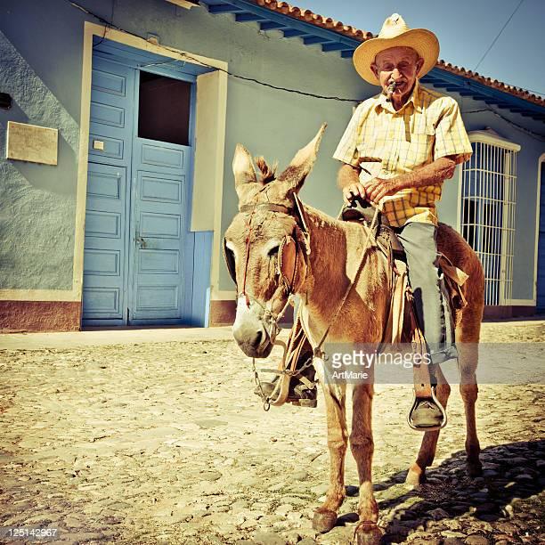 Cuban senior man riding his donkey