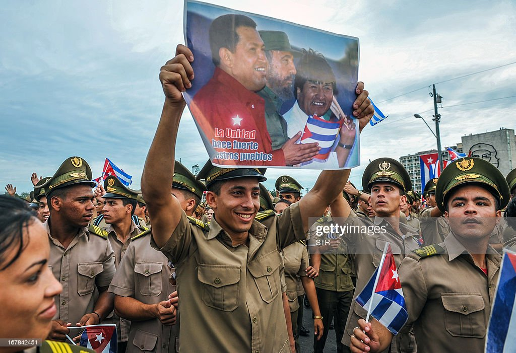 A Cuban soldier of the Revolutionary Armed Forces (FAR) shows a poster with portraits of Venezuelan late president Hugo Chavez (L), former Cuban president Fidel Castro (C) and Bolivian president Evo Morales during May Day celebrations at Revolution Square in Havana on May 1, 2013. About half a million people across Cuba took part in May Day celebrations dedicated to the late Venezuelan president Hugo Chavez, a close ally of the island's communist leaders. President Raul Castro, 81, reviewed a parade in Havana of some 300,000 people bearing banners and flags, from stands erected in the Plaza of the Revolution alongside a giant portrait of Chavez.