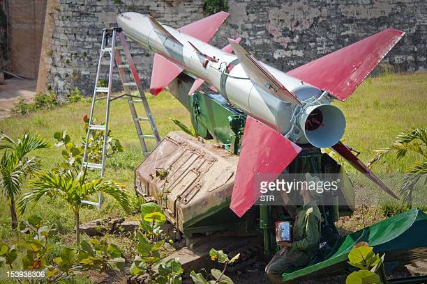 A Cuban soldier paints a SAM2 missile deployed during the missile crisis of 1962 at Morro Cabana complex on October 11 2012 in Havana Cuba celebrates...
