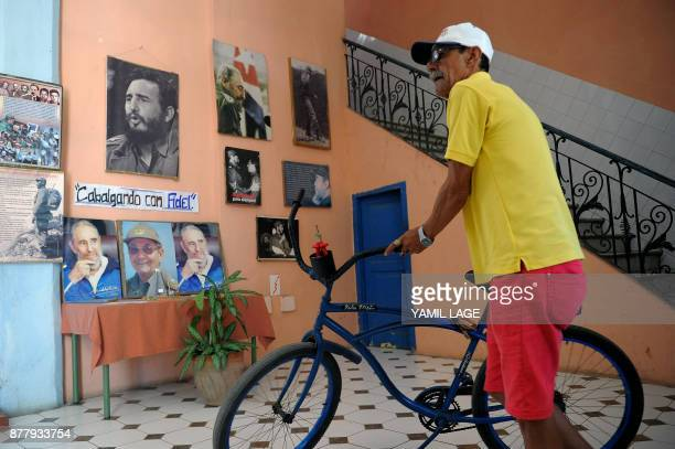 A Cuban stands with his bicycle next to a wall decorated with posters of late Cuban leader Fidel Castro in Havana on November 23 2017 Cuba...