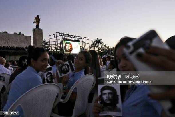 Cuban students hold images of Che Guevara and take selfies prior to a political act at the Plaza de la Revolucion to celebrate the 50th anniversary...