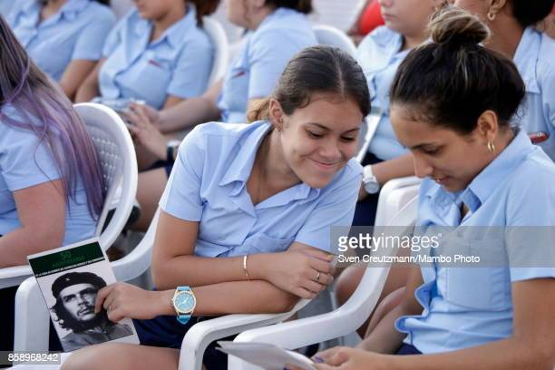 Cuban students hold images of Che Guevara prior to a political act at the Plaza de la Revolucion to celebrate the 50th anniversary of the death of...