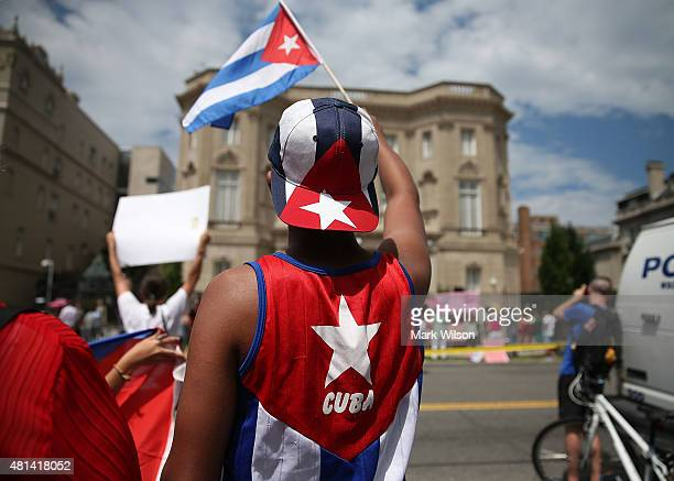 Cuban supporter Danial Espino Delgado waves a Cuban flag in front of the country's embassy after it reopened for the first time in 54 years July 20...