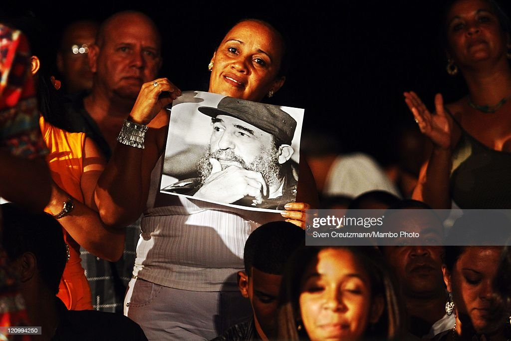 A Cuban supporter holds up a photo of Cuban Revolution leader Fidel Castro as she dances during a concert of international artists on the eve of the 85th birthday of Cuba's Revolution leader Fidel Castro in the Teatro Karl Marx August 12, 2011 Havana, Cuba. The three hour 'Serenade for Fidelity' (Serenata a la Fidelidad) was organized by the Foundation Guayasemin from Ecuador and the Cuba Ministry of Culture. Fidel Castro fell ill in July 2006 and has stepped back from power, handing over power to his younger brother Raul Castro.