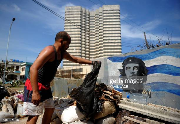 A Cuban throws garbage near a wall with a graffiti of Che Guevara and a Cuban flag during the cleanup after the passage of Hurricane Irma in Havana...