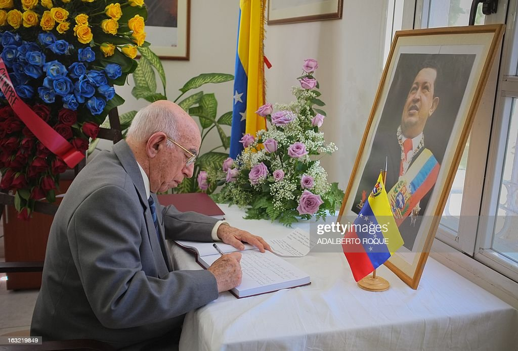 Cuban vice president Jose Ramon Machado Ventura signs the book of condolences for deceased Venezuelan President Hugo Chavez at the Venezuelan embassy in Havana, on March 6, 2013. The flag-draped coffin of the Venezuelan leader was borne through throngs of weeping supporters on Wednesday as a nation bade farewell to the firebrand leftist who led them for 14 years. AFP PHOTO/ADALBERTO ROQUE