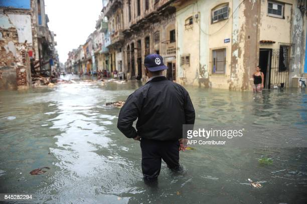 A Cuban wades through a flooded street in Havana on September 10 2017 Deadly Hurricane Irma battered central Cuba on Saturday knocking down power...