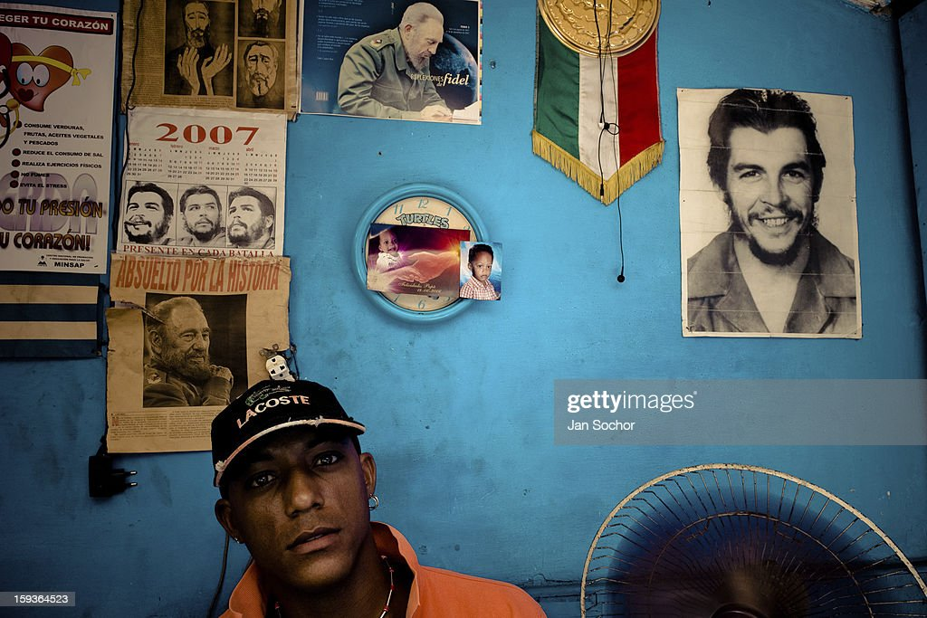 A Cuban watchmaker works in front of a wall covered by pictures of the Cuban Revolutionary leaders in Havana, Cuba, 16 August 2008 in Havana, Cuba. During the Cuban Revolution, an armed rebellion at the end of the 1950s, most of the revolutionary leaders started as unnamed soldiers fighting from the jungle. After taking over the power, they became autocratic rulers holding almost absolute power and pursuing the opposition. For some reason Cuban people never stopped to worship Fidel Castro, Che Guevara, Raul Castro and others. Cubans hang their photos and portraits on the wall at home, shops and working places even when they don't have to.