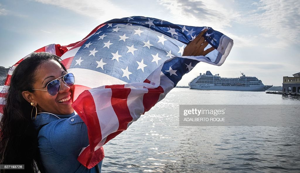 A Cuban waves a US flag at the Malecon waterfront as the first US-to-Cuba cruise ship to arrive in the island nation in decades glides into the port of Havana, on May 2, 2016. The first US cruise ship bound for Cuba in half a century, the Adonia -- a vessel from the Carnival cruise's Fathom line -- set sail from Florida on Sunday, marking a new milestone in the rapprochement between Washington and Havana. The ship -- with 700 passengers aboard -- departed from Miami, the heart of the Cuban diaspora in the United States. / AFP / ADALBERTO