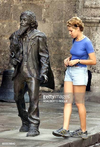 A Cuban woman is seen observing the new 'Caballero de Paris' statue in La Habana Cuba 25 October 2001 Una cubana observa la nueva estatua del llamado...