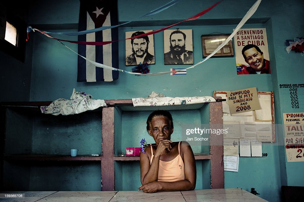 A Cuban woman stands behind the shop counter, holding a flower, in front of a wall covered by photos of the revolutionary leaders, Santiago de Cuba, Cuba, 31 July 2008 in Havana, Cuba. During the Cuban Revolution, an armed rebellion at the end of the 1950s, most of the revolutionary leaders started as unnamed soldiers fighting from the jungle. After taking over the power, they became autocratic rulers holding almost absolute power and pursuing the opposition. For some reason Cuban people never stopped to worship Fidel Castro, Che Guevara, Raul Castro and others. Cubans hang their photos and portraits on the wall at home, shops and working places even when they don't have to.