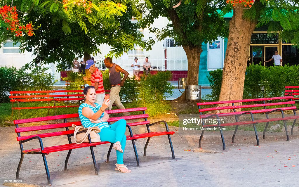 Cuban woman using IMO app in public Etecsa wifi area early in the morning Public wifi areas are the first contact of Cubans with internet Series...