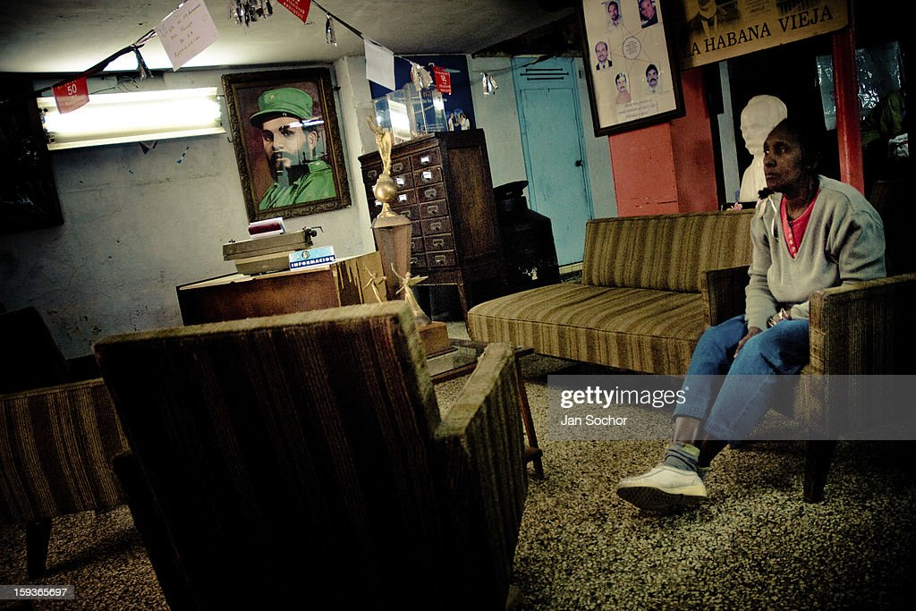 A Cuban woman waits, sitting on a sofa, in an entrance room to the Cuban state office in Havana, Cuba, 4 February 2009 in Havana, Cuba. During the Cuban Revolution, an armed rebellion at the end of the 1950s, most of the revolutionary leaders started as unnamed soldiers fighting from the jungle. After taking over the power, they became autocratic rulers holding almost absolute power and pursuing the opposition. For some reason Cuban people never stopped to worship Fidel Castro, Che Guevara, Raul Castro and others. Cubans hang their photos and portraits on the wall at home, shops and working places even when they don't have to.