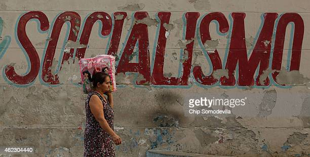 Cuban woman walks home from the market past a mural painted by the Committee for the Defense of the Revolution along San Lazaro Street in the Vedado...
