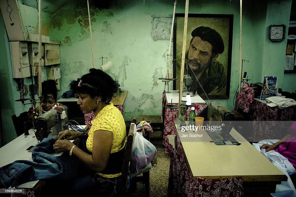 Cuban women work in front of a large portrait of the Revolutionary leader Che Guevara, hung on the wall of dress-maker's in Havana, Cuba, 13 February 2009. During the Cuban Revolution, an armed rebellion at the end of the 1950s, most of the revolutionary leaders started as unnamed soldiers fighting from the jungle. After taking over the power, they became autocratic rulers holding almost absolute power and pursuing the opposition. For some reason Cuban people never stopped to worship Fidel Castro, Che Guevara, Raul Castro and others. Cubans hang their photos and portraits on the wall at home, shops and working places even when they don't have to.
