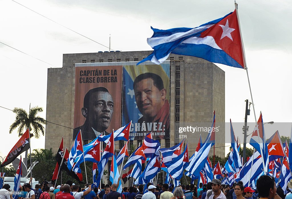 Cuban workers attend May Day celebrations next to portraits of Venezuelan late president Hugo Chavez (R) and Cuban union leader Lazaro Peña (1911-1974) at Revolution Square in Havana on May 1, 2013. About half a million people across Cuba took part in May Day celebrations dedicated to the late Venezuelan president Hugo Chavez, a close ally of the island's communist leaders. President Raul Castro, 81, reviewed a parade in Havana of some 300,000 people bearing banners and flags, from stands erected in the Plaza of the Revolution alongside a giant portrait of Chavez.