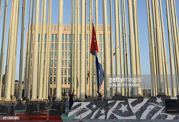 Cuban workers hoist a Cuban flag in front of the US Embassy in Havana on July 20 2015The United States and Cuba formally resumed diplomatic relations...
