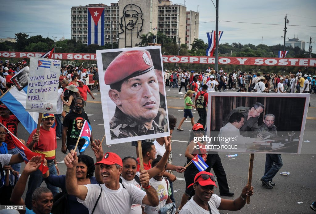 Cuban workers show a portrait of Venezuelan late President Hugo Chavez during May Day celebrations at Revolution Square in Havana on May 1, 2013.