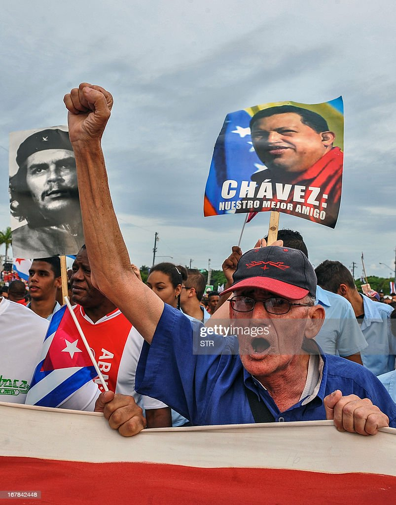 Cuban workers show portraits of Venezuelan late president Hugo Chavez (R) and Argentine born guerrilla leader Ernesto Che Guevara during May Day celebrations at Revolution Square in Havana on May 1, 2013. About half a million people across Cuba took part in May Day celebrations dedicated to the late Venezuelan president Hugo Chavez, a close ally of the island's communist leaders. President Raul Castro, 81, reviewed a parade in Havana of some 300,000 people bearing banners and flags, from stands erected in the Plaza of the Revolution alongside a giant portrait of Chavez.