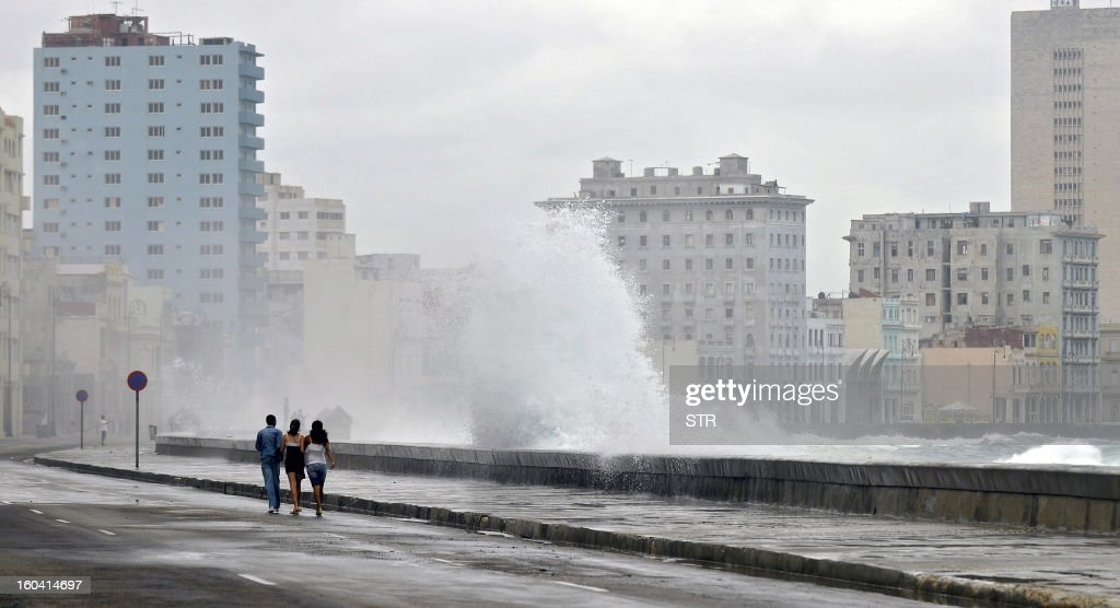 Cuban youngsters walk while a giant wave hits the seafront in Havana on November 16, 2008
